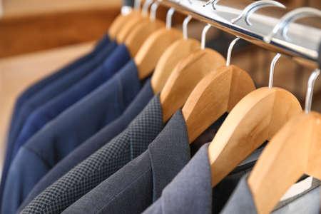 Photo pour Hanger with different stylish male suits, closeup - image libre de droit