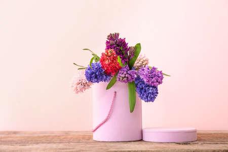 Photo pour Box with beautiful hyacinth flowers on table against color background - image libre de droit