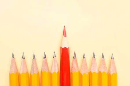 Foto de Red pencil among ordinary ones on color background. Concept of uniqueness - Imagen libre de derechos