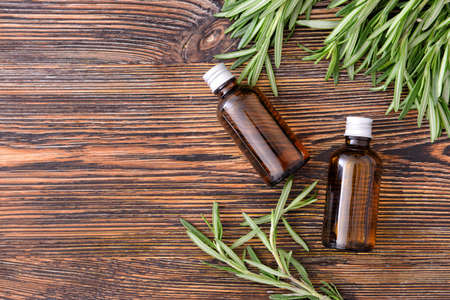 Photo for Bottles of rosemary essential oil on table - Royalty Free Image