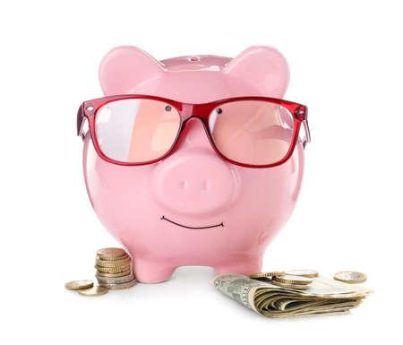 Foto de Piggy bank with glasses and money on white background - Imagen libre de derechos