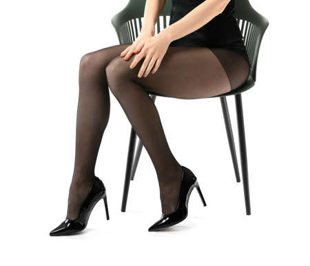 Photo pour Beautiful young woman in tights sitting on chair against white background - image libre de droit