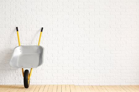 Photo for Empty wheelbarrow near white brick wall - Royalty Free Image