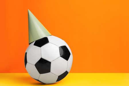 Foto de Soccer ball and party cone on color background - Imagen libre de derechos