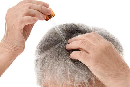 Photo pour Senior woman using serum for hair loss treatment on white background, closeup - image libre de droit