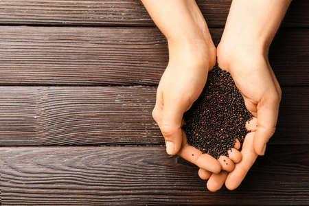 Photo pour Female hands with healthy quinoa on wooden background - image libre de droit