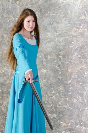 Pretty young woman with long hair in historical medieval blue dress poses in studio with sword