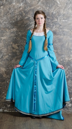 Pretty young woman in historical medieval blue dress poses in studio