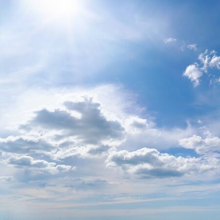 Bright summer sun on blue sky with white clouds.