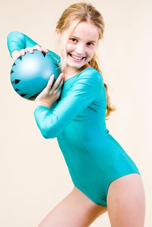 Teenage gymnast with ball on grey background
