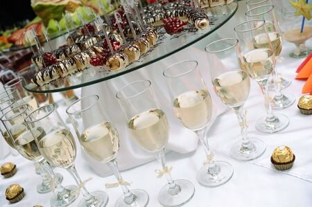 Row of glasses of white wine and sweets