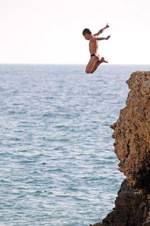 Photo pour an expressive boy is diving into the sea - image libre de droit
