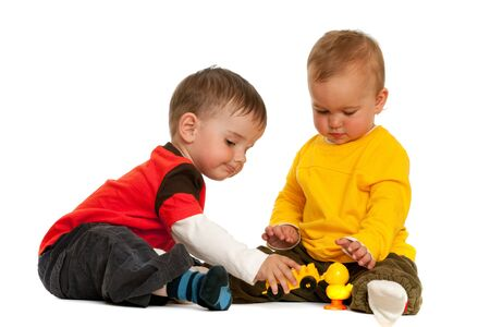 Two children are playing with blocks; isolated on the white background