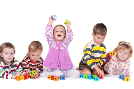 Five children are playing vivid blocks with letters; isolated on the white background