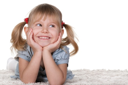 Photo pour A cheerful little girl with funny tails is lying on the white carpet; isolated on the white background - image libre de droit