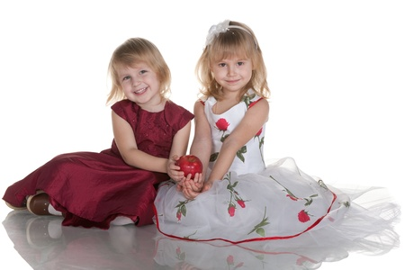 Two cheerful girls in ball dresses are holding a red apple together; isolated on the white background