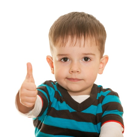 A closeup portrait of a cheerful little boy holding his thumb up; isolated on the white background
