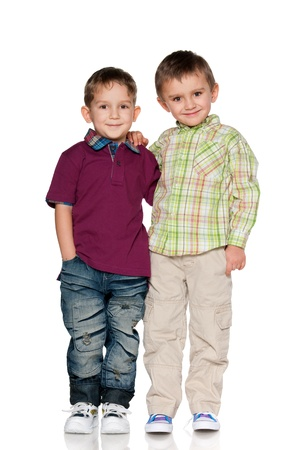 Two boys are standing together; isolated on the white background
