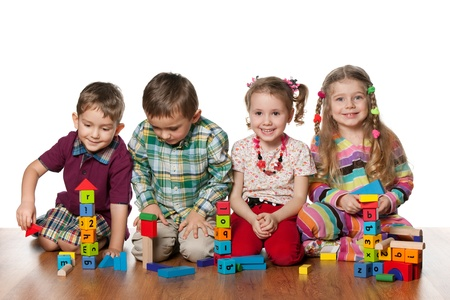 Foto de Four children are playing on the floor together; isolated on the white background - Imagen libre de derechos