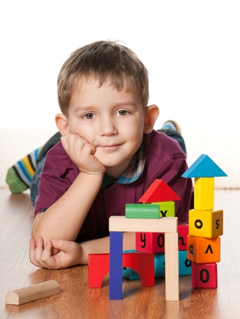 A little boy is lying on the floor near toys; on the white background