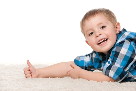 A smiling little boy is lying on the white carpet and holding his thumb up