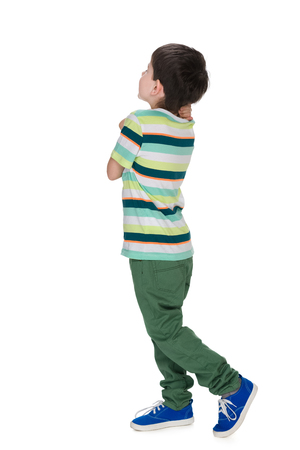 Photo for A little boy in a striped shirt looks back against the white background - Royalty Free Image