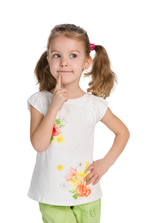 Photo for A curious little girl stands against the white background and thinks - Royalty Free Image