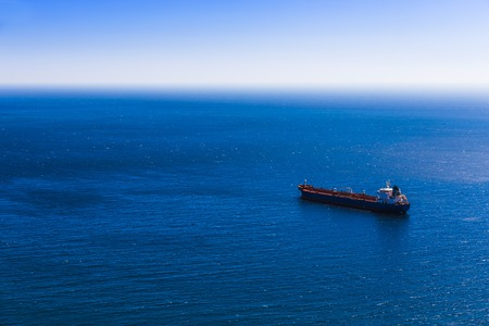 Empty container cargo ship in the blue sea. Aerial view