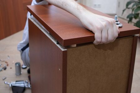 Foto de A male tool collects furniture color spanish walnut. Assembly of a desk drawer cover. - Imagen libre de derechos