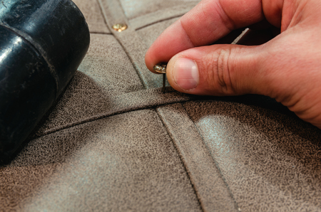 Photo pour Furniture production, upholstery of upholstered furniture, decorative nails on the background of fabric upholstery close-up. - image libre de droit