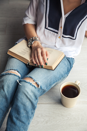 Young modern girl in torn jeans reading a book with a big cup of coffee. Fashion, lifestyle, lifestyle, recreation, education, hobbies.