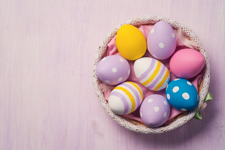 Photo for Colorful Easter eggs in a basket, with space for text. Top view - Royalty Free Image