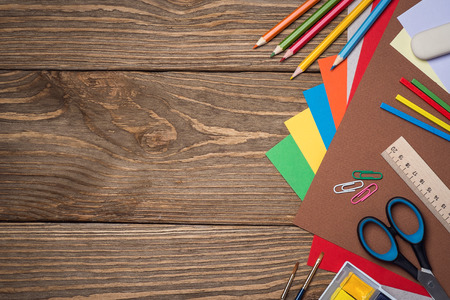 School supplies on a wooden table with space for text, top view