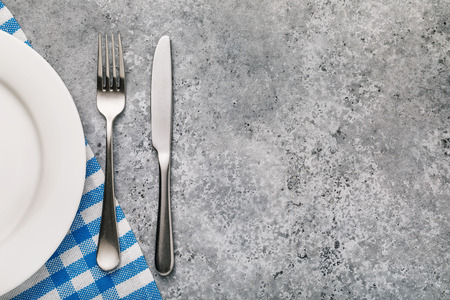 Foto de Fork, knife and white plate on a table with texture of concrete, top view. Food background - Imagen libre de derechos