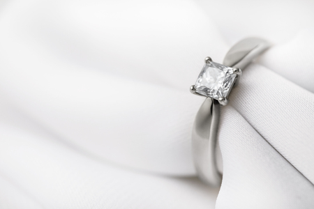 Photo pour White gold wedding ring with a large diamond on a silk fabric with copy space, close-up - image libre de droit