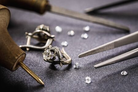 Photo pour Earrings with a stone on the table, surrounded by tools for the repair of jewelry - image libre de droit