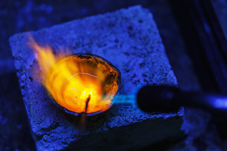 Melting of gold in crucible, close-up. Workflow in a jewelry workshop