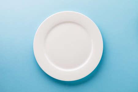 Photo pour Flat ceramic plate white on a blue background, top view. Food background - image libre de droit