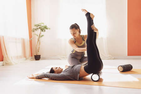 Photo for Myofascial release, the trainer shows the student the correct work with the sacrum and abs with the help of a massage roller. - Royalty Free Image