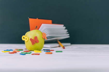 Photo pour Concept Back to School. Green apple with colored letters and notepad background - image libre de droit