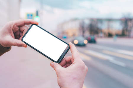 Photo for A man holds a mock-up of a smartphone with a white screen on the background of the road - Royalty Free Image