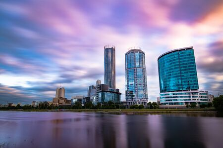 Photo for Beautiful wide angle long exposure cityscape of Yekaterinburg city, Russia at sunset with blurred blue and purple clouds. Skyscrapers reflecting in water of Iset river - Royalty Free Image