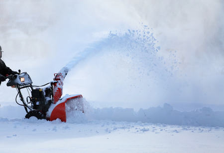Foto de man working with snow blower after winter storm in city - Imagen libre de derechos