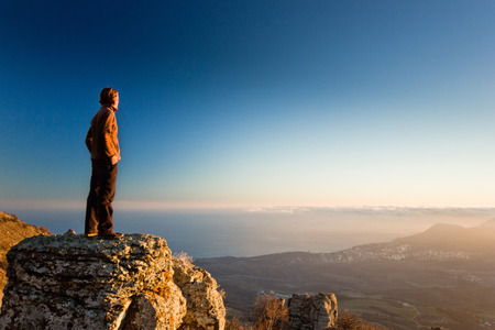 thinking man on the cliff in mountains at sunset with blue sky
