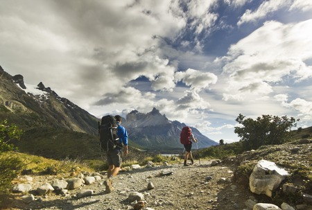 two men with backpack hiking in patagonia mountains, torres del paine