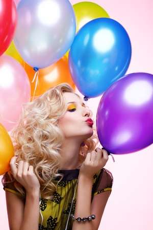portrait of beautiful blonde girl with balloons celebrating birthday