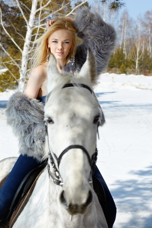 Young blond beautiful woman with light gray horse
