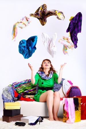Photo pour portrait of happy young shopaholic woman sittin on sofa wit purchases around and juggling clothes  - image libre de droit