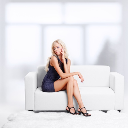 full-length portrait of beautiful young blond woman on couch with white furs on floor