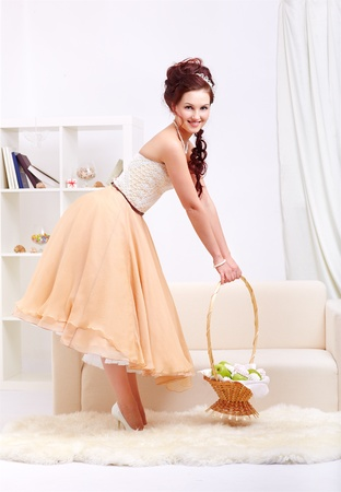 full-length portrait of young beautiful retro woman in vintage skirt with petticoat and corset wtanding with basket of green apples and marshmallows